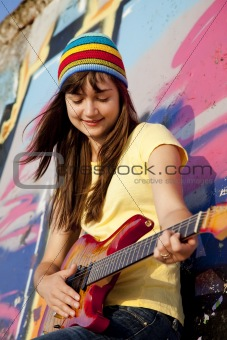 Beautiful brunette girl with guitar and graffiti wall at backgro