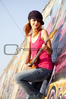 Beautiful red-haired girl with guitar and graffiti wall at backg