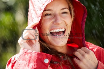 Young female holding a raincoat hat on head - Enjoying rain
