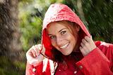 Young girl wearing a raincoat enjoying the rain