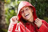 Pretty young woman in raincoat enjoying the rain
