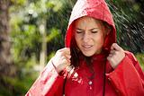 Cute teeange girl in raincoat standing outside in rain