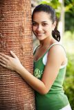 Pretty young woman hugging a big tree in a park