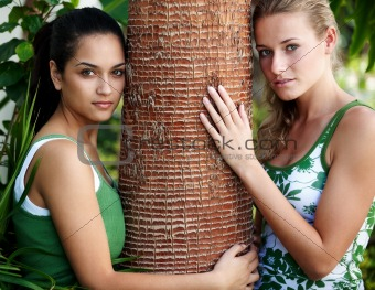 Beautiful teenage girls holding a tree bark in a park