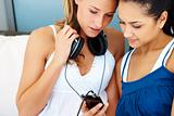 Young female friends listening to music on mobile phone