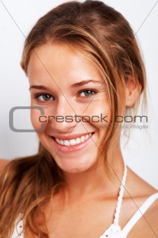 Happy teenage girl smiling on white background