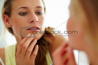 Cute young woman looking her face in the mirror