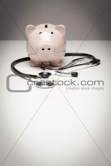 Piggy Bank and Stethoscope with Selective Focus on a Gradated Background.