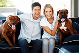 Happy young couple sitting with their pet on couch