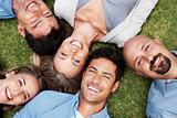 People together lying on grass with a smile