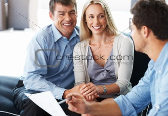 Expert advice - Smiling young couple listening to male consultan