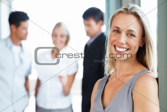 Smiling businesswoman with her colleagues in background