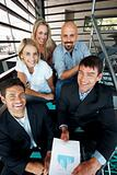 Smiling group of businespeople sitting together on staircase