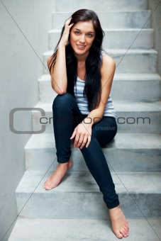 Pretty young woman sitting casually on steps
