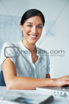 Smart young business woman at her desk
