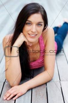 Pretty young woman lying on wooden floor