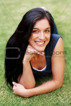 Happy young lady lying on grass at the park