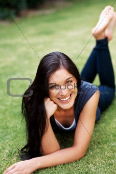 Smiling young girl relaxing on grass at the park