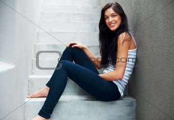 Beautiful young female sitting on the staircase