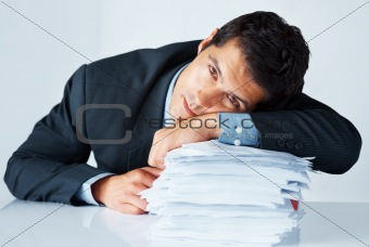Exhausted businessman resting on stack of paperwork