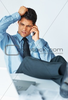 Confused executive having phone conversation