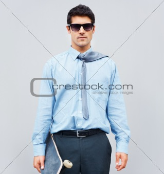 Confident businessman with skateboard