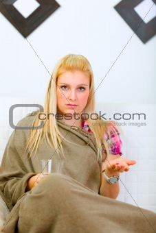 Ill woman sitting wrapped in woolen plaid with glass of water and pill