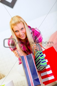 Smiling beautiful woman sitting on sofa and holding shopping bags in hands