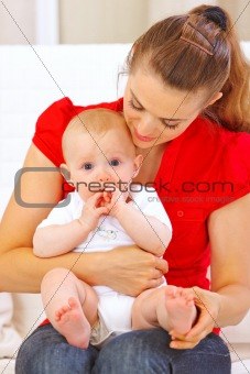 Baby putting his hands in mouth while sitting on mother laps