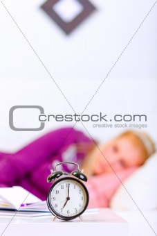Alarm clock on table and woman laying on sofa in background