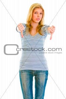 Upset teen girl showing thumbs down gesture