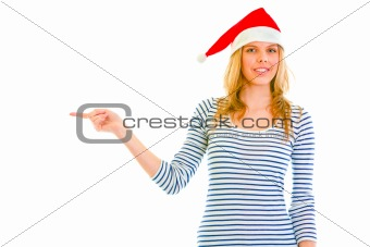 Beautiful teen girl in Santa hat pointing in corner