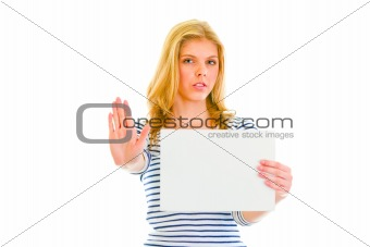 Beautiful teen girl holding blank paper sheet and showing stop gesture