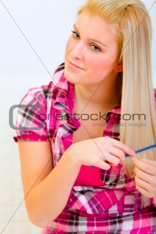 Portrait of pretty woman combing hair
