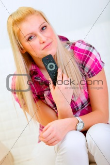 Portrait of happy young woman with TV remote control