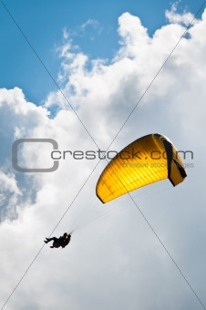Yellow parachute against sky and clouds