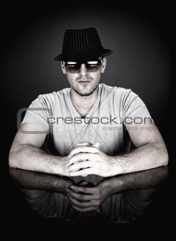 man in hat and sunglasses sitting behind desk looking at camera