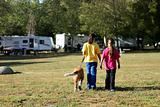 Girls Walking a Dog While Camping