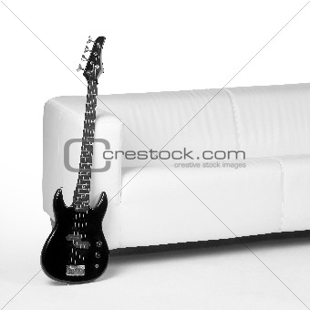 black bass guitar and white couch