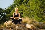 Woman meditating open hand yoga on rock