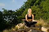 Eyes closed woman meditating yoga on rock