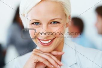 Smart businesswoman smiling with colleagues in background 