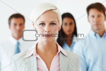 Smart businesswoman standing in front of his team