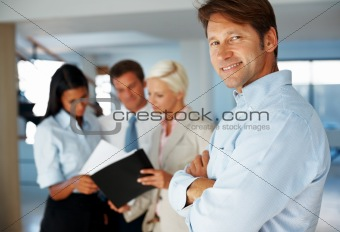 Successful executive with colleagues working at the back