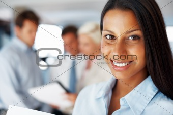 Confident young businesswoman smiling at office