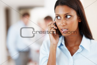 Thoughtful female executive using cellphone
