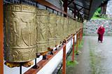 Buddhist monk and prayer wheels in a row