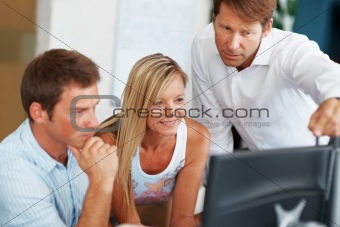 Team of business colleagues working on computer