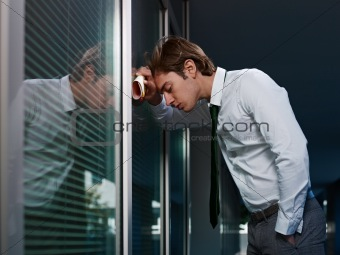 sad businessman leaning on window in office