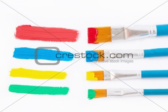 Art brushes in colored inks.On a white background